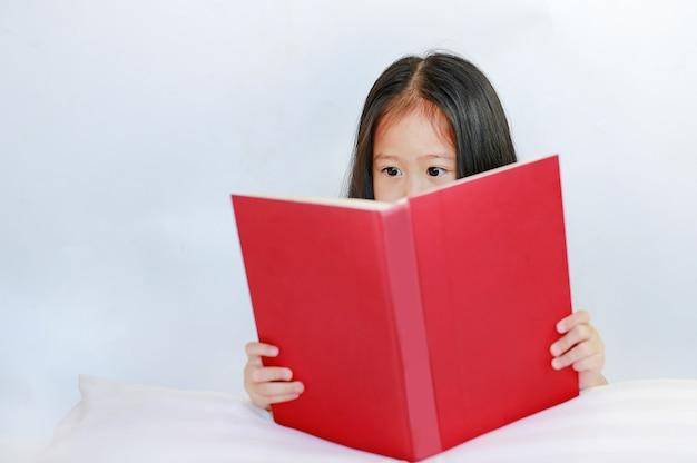 Belle petite fille asiatique enfant lisant un livre relié, couché avec oreiller sur fond blanc.