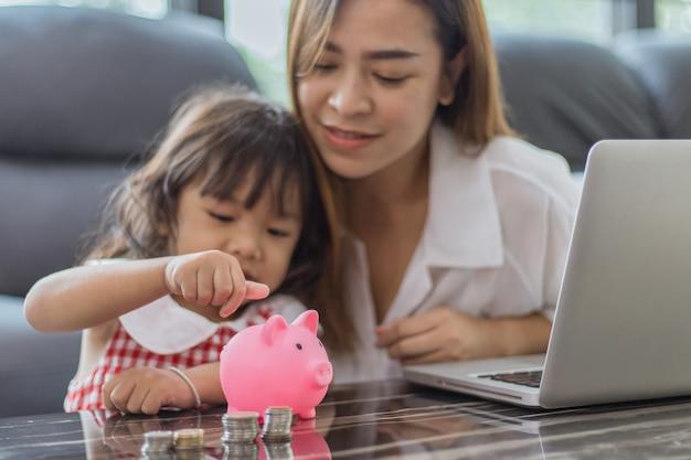 Belle petite fille asiatique et sa mère mettent de l'argent dans sa tirelire pour économiser