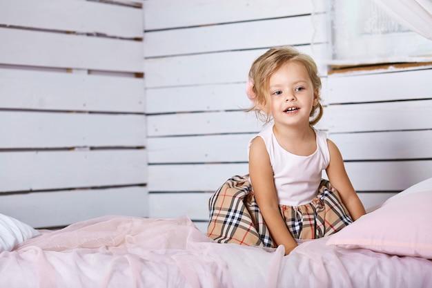 Belle petite fille assise sur le lit.