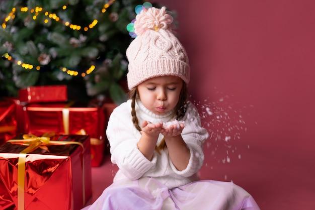 Belle petite fille au chapeau jouant avec la neige près de cadeaux et de sapin de noël