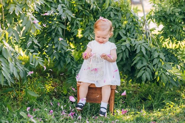 Belle petite fille aux cheveux blonds dans une robe blanche assise sur une chaise dans la journée d'été ensoleillée du parc.