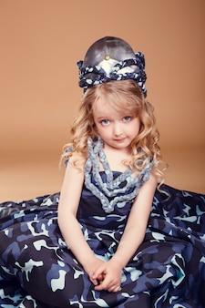Belle petite fille aux cheveux blonds à la mode des vêtements militaires