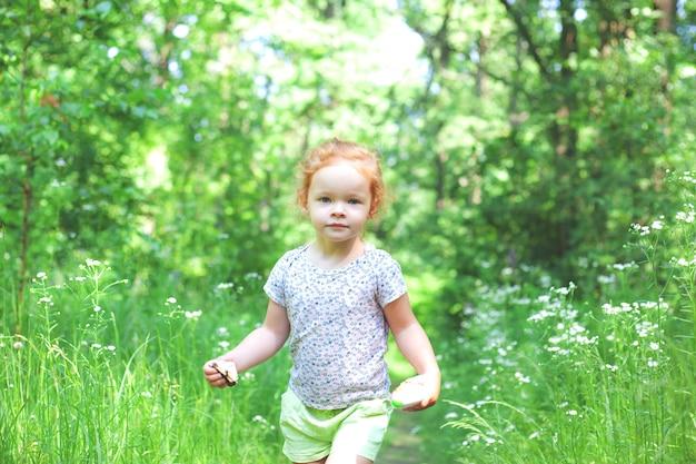 Une belle petite fille aux cheveux roux clair marche le long d'un sentier dans la forêt
