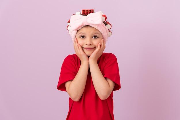 Une belle petite fille en bigoudis tient ses joues et sourit