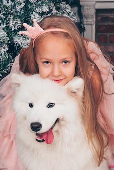 Belle petite fille blonde sourit avec un chien samoyède drôle blanc