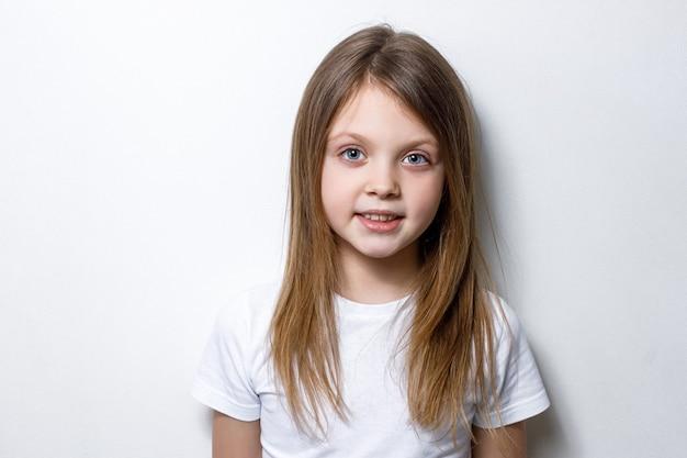 Une belle petite fille en bonne santé en vêtements blancs sourit