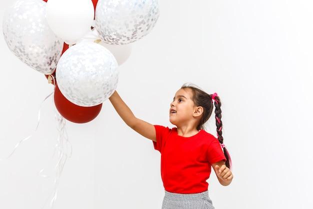 Belle petite fille avec des boules sur blanc