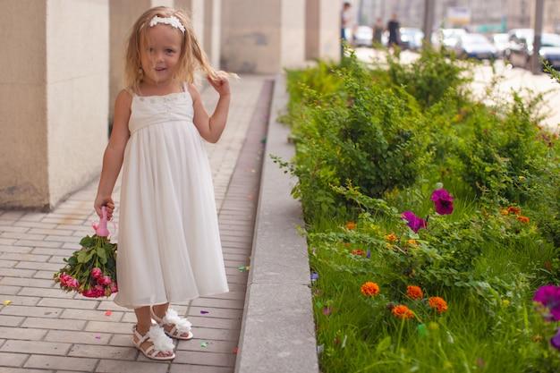 Belle petite fille avec bouquet de roses à la main lors du mariage