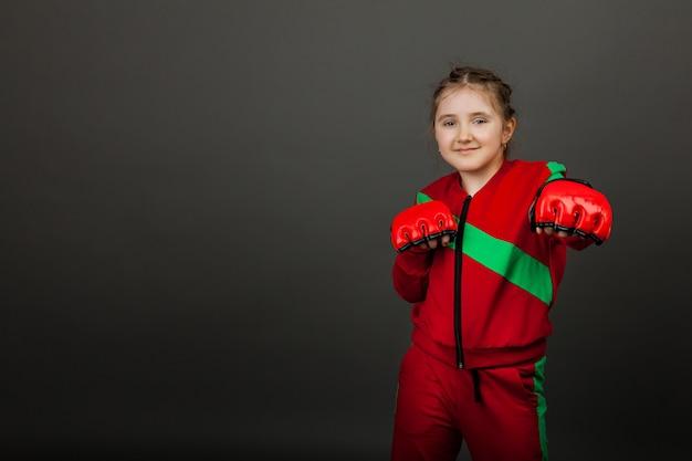 Belle petite fille boxer dans des gants prêts à se battre.