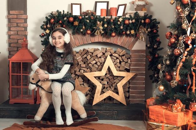 Belle petite fille brune aux cheveux longs, assise sur un cheval de jouet à la salle décorée de noël.