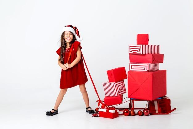 Belle petite fille brune dans un costume de père noël porte des cadeaux de noël sur un espace de traîneau pour tex