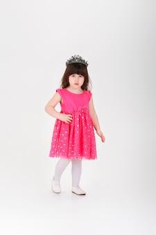 Belle petite fille brune en robe de princesse rose avec une couronne sur fond gris. bébé mignon