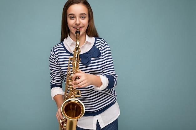 Belle petite fille brune souriante et heureuse portant une chemise à manches longues à rayures isolées sur bleu