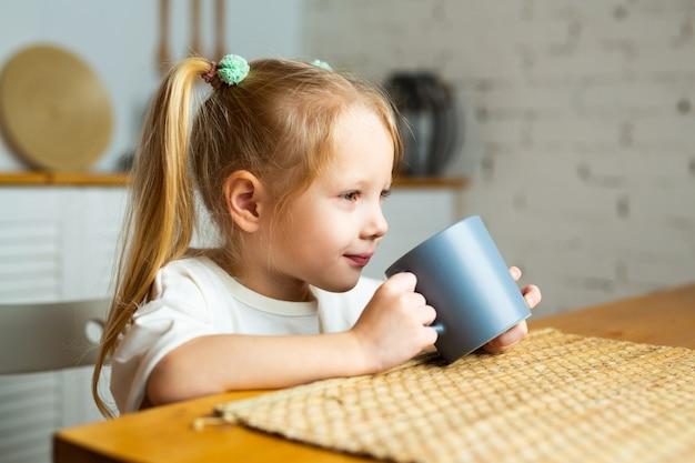 Belle petite fille buvant du thé dans la cuisine