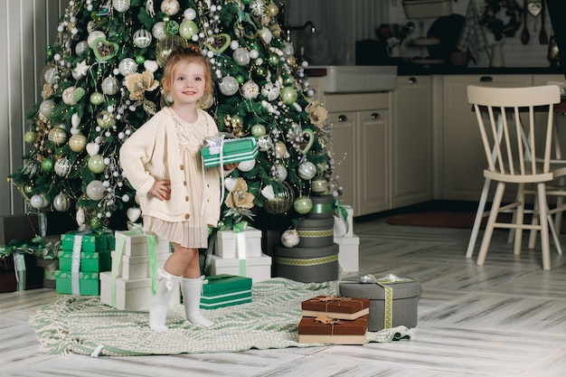Belle petite fille avec un cadeau à la main près de l'arbre de noël