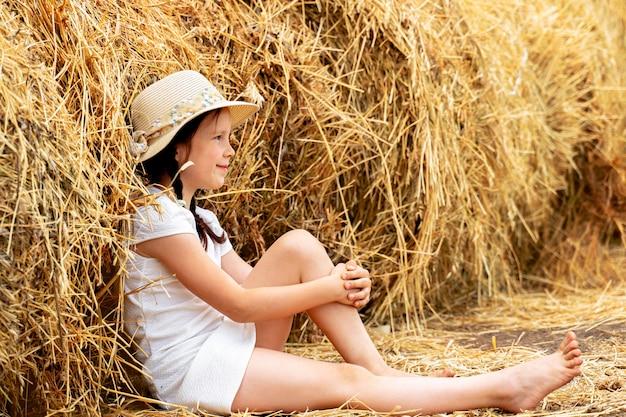 Belle petite fille avec un chapeau sur le foin