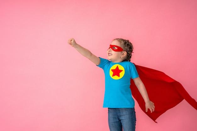 Belle petite fille en costume de super-héros en cape rouge et masque montre à quel point