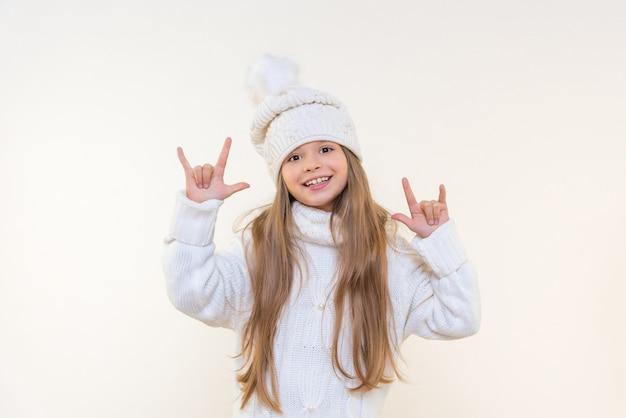 Une belle petite fille dans un chapeau d'hiver et un pull sur fond blanc isolé est très heureuse et pointe ses doigts sur le côté