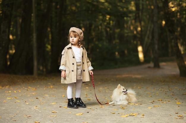 Belle petite fille dans un manteau beige et un béret avec un petit chien moelleux en laisse se tient debout