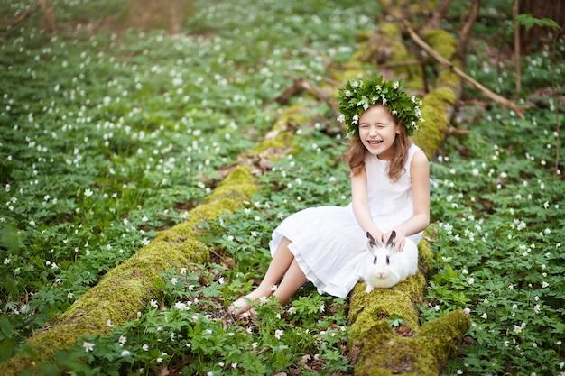 Belle petite fille dans une robe blanche plaing avec lapin blanc dans le bois de printemps.