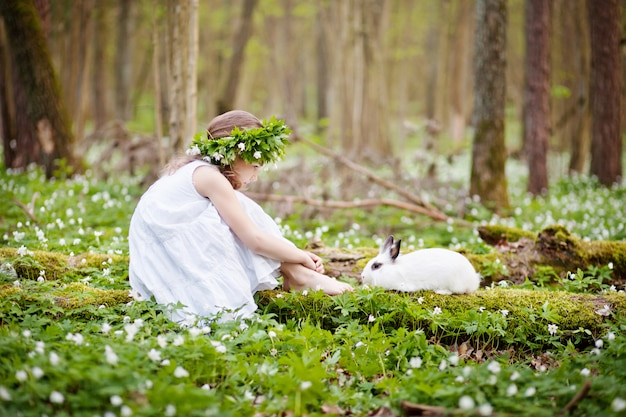 Belle petite fille dans une robe blanche plaing avec un lapin blanc dans la forêt de printemps