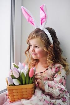 Belle petite fille dans une robe élégante est assise sur un rebord de fenêtre avec un bouquet de fleurs de tulipes sur une surface de fenêtre.