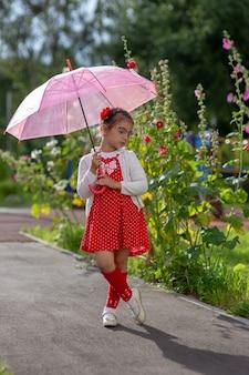 Une belle petite fille dans une robe rouge et un chemisier blanc sous un parapluie rose se dresse un jour d'été.