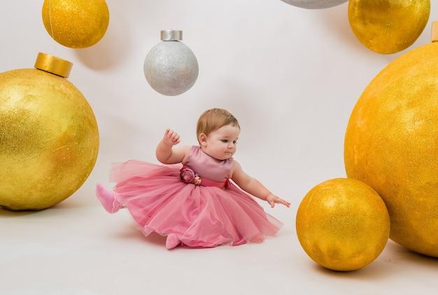 Une belle petite fille dans une robe tutu rose est assise sur un mur blanc avec d'énormes ballons