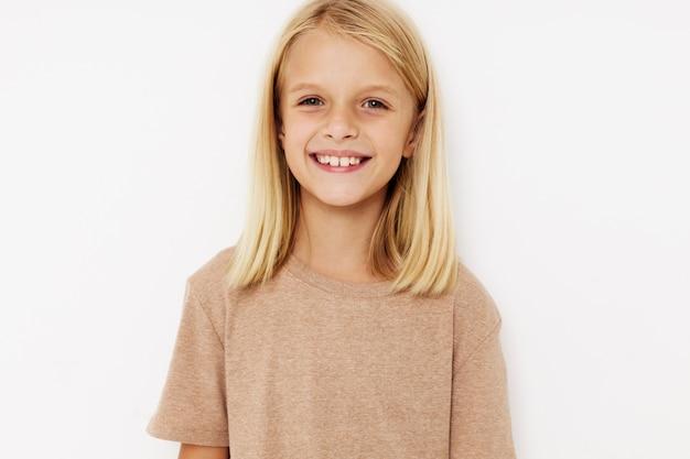 Belle petite fille dans un tshirt beige fond isolé