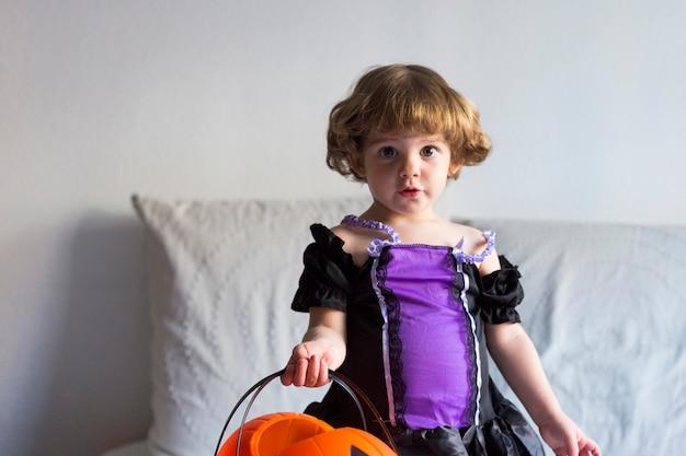 Belle petite fille debout sur le lit et portant un costume d'halloween. jouer avec des citrouilles