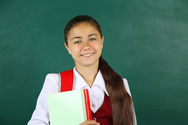 Belle petite fille debout près du tableau noir en classe