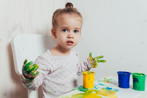 Belle petite fille dessine avec des peintures au doigt sur une feuille de papier blanc