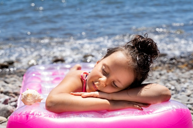 Une belle petite fille dort sur un matelas de bain au bord de la mer.