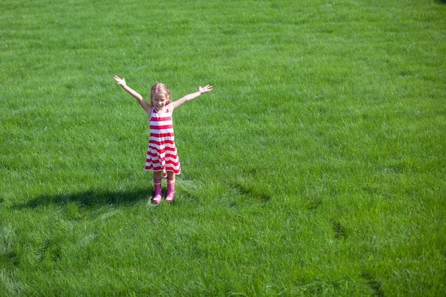 Belle petite fille écarte les bras sur la pelouse