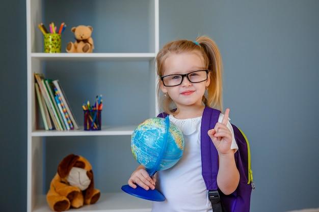 Belle petite fille de l'école élémentaire tenant un livre et un globe. concept de l'éducation. le jour du professeur. jour du livre.