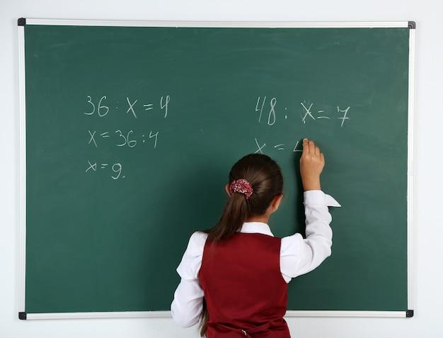 Belle petite fille écrit sur le tableau noir en classe