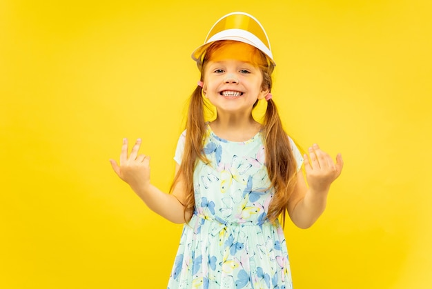 Belle petite fille émotionnelle isolée sur fond jaune. portrait demi-longueur d'enfant heureux et célébrant vêtu d'une robe et d'un bonnet orange. concept d'été, émotions humaines, enfance.
