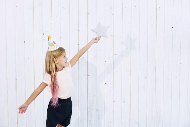 Belle petite fille d'enfant dans un chapeau de fête et un oreiller d'étoile sur le fond en bois blanc