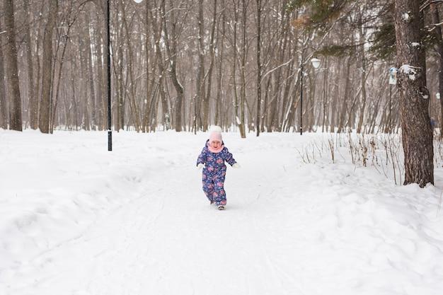 Belle petite fille enfant s'amuser dans le parc d'hiver