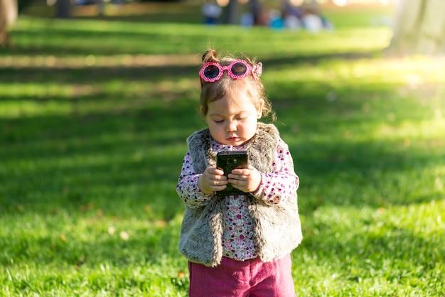 Belle petite fille enfant utilisant un téléphone portable à l'extérieur.