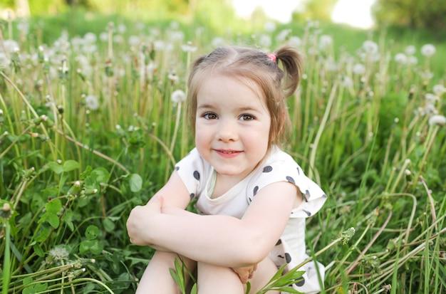 Une belle petite fille est assise sur l'herbe dans un champ de printemps parmi les pissenlits en plein air, profitant de la nature. le concept de liberté