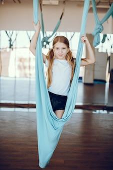 Une belle petite fille est engagée dans une salle de sport