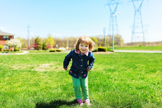 Belle petite fille à l'extérieur en journée ensoleillée jolie petite fille jouant