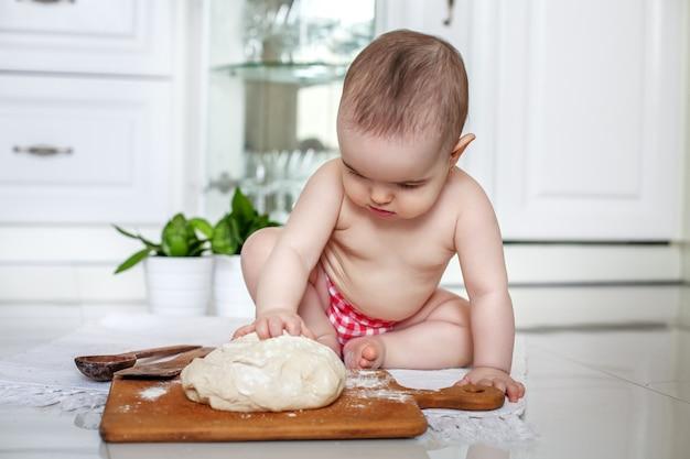Belle petite fille fait des rouleaux de pâte dans la cuisine