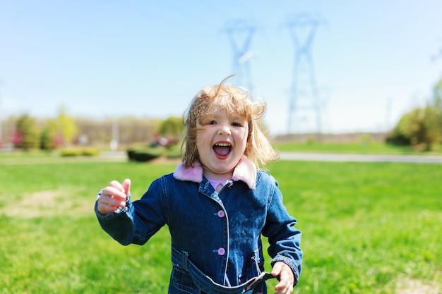 Belle petite fille avec une fleur sur la tête à l'extérieur en journée ensoleillée jolie petite fille jouant à l'extérieur au printemps