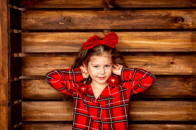 Belle petite fille gaie en pyjama de noël à carreaux rouges tenant des boules de noël sur un fond en bois