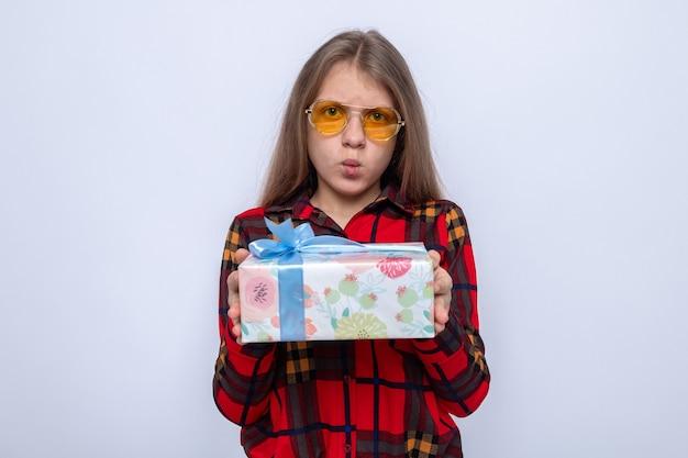 Belle petite fille inquiète portant une chemise rouge et des lunettes tenant un cadeau
