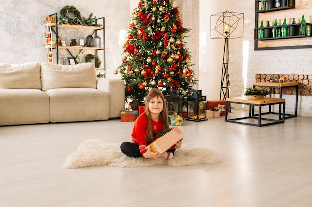Belle petite fille jouant avec un cadeau de noël, arbre de noël