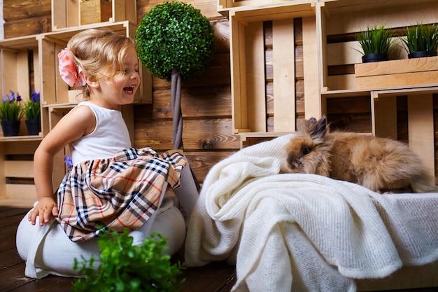 Belle petite fille jouant avec le lapin.