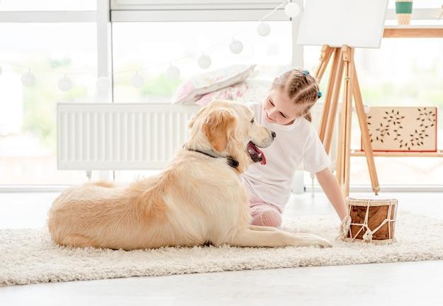 Belle petite fille jouant de la musique avec un beau chien à l'intérieur